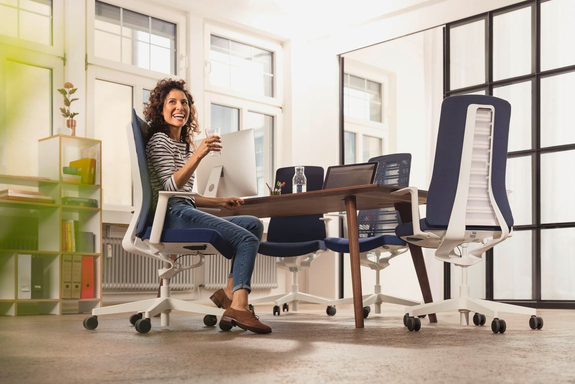 woman sitting on a comfortable office chairin a brightly lit conference room