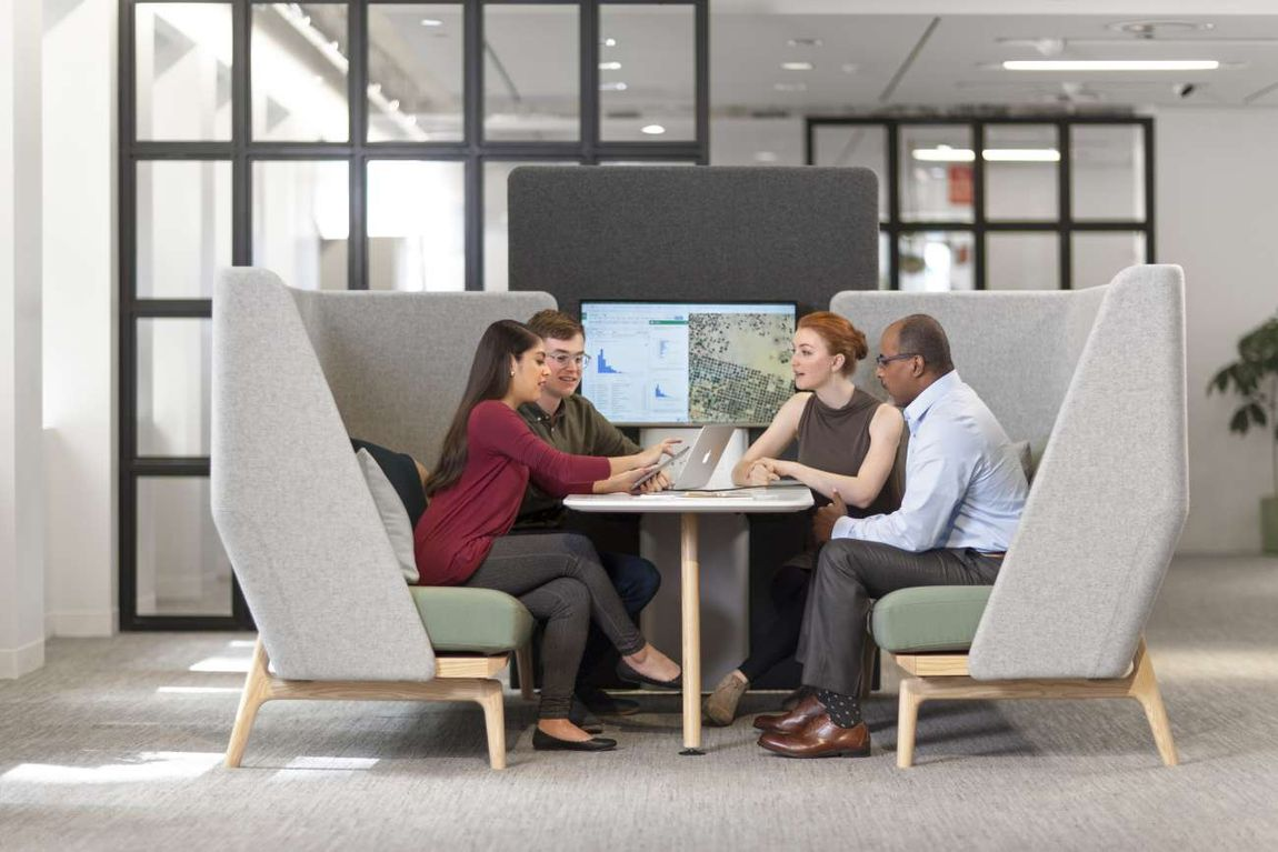 Four coworkers sitting around table at acoustic furniture