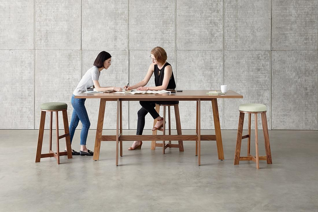 Two employees sharing multipurpose work table.