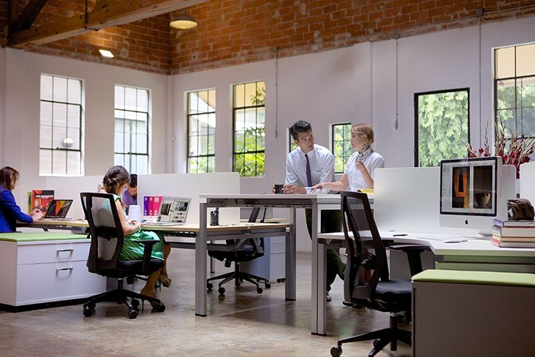Workers standing and sitting in hybrid workspace.