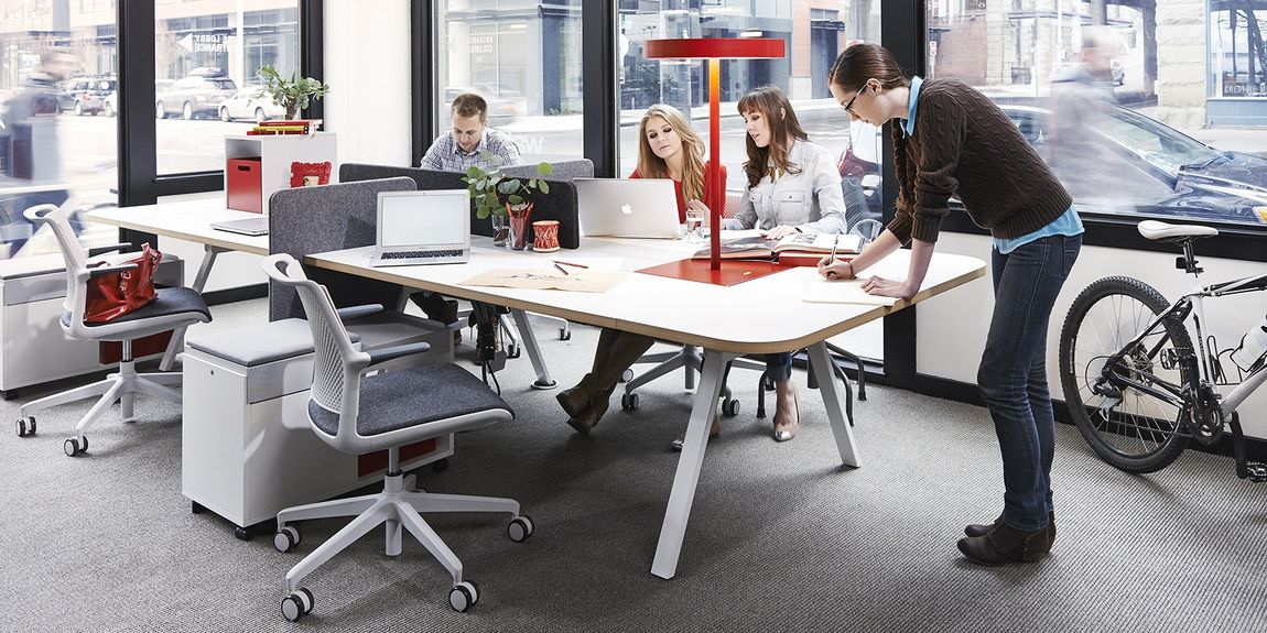 People at work around collaborative desk in front of big windows with light