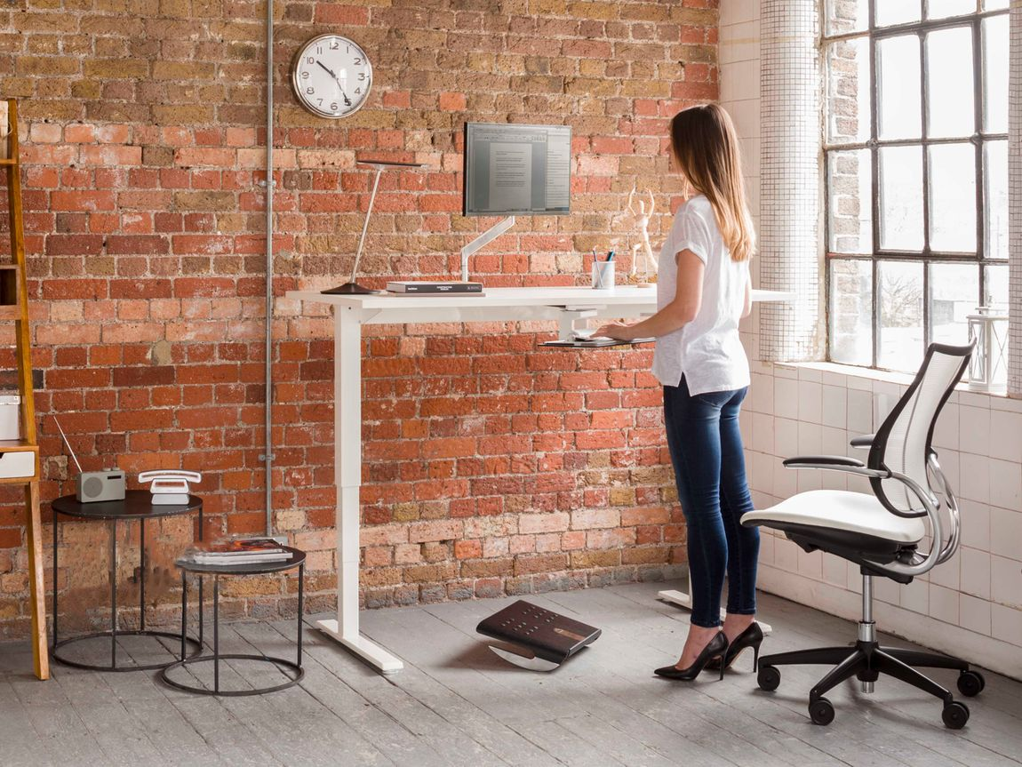 Slender woman standing at sit-stand desk