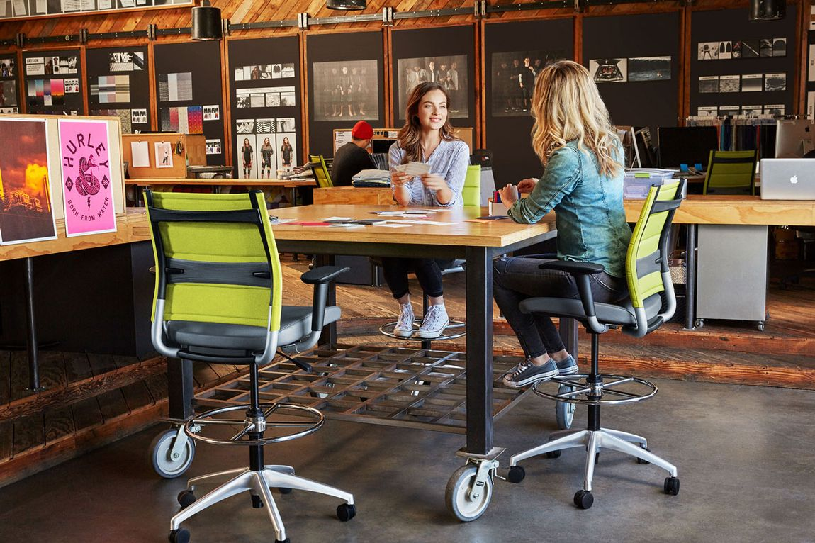 Two women gathered around modern office table with ergonomic chairs