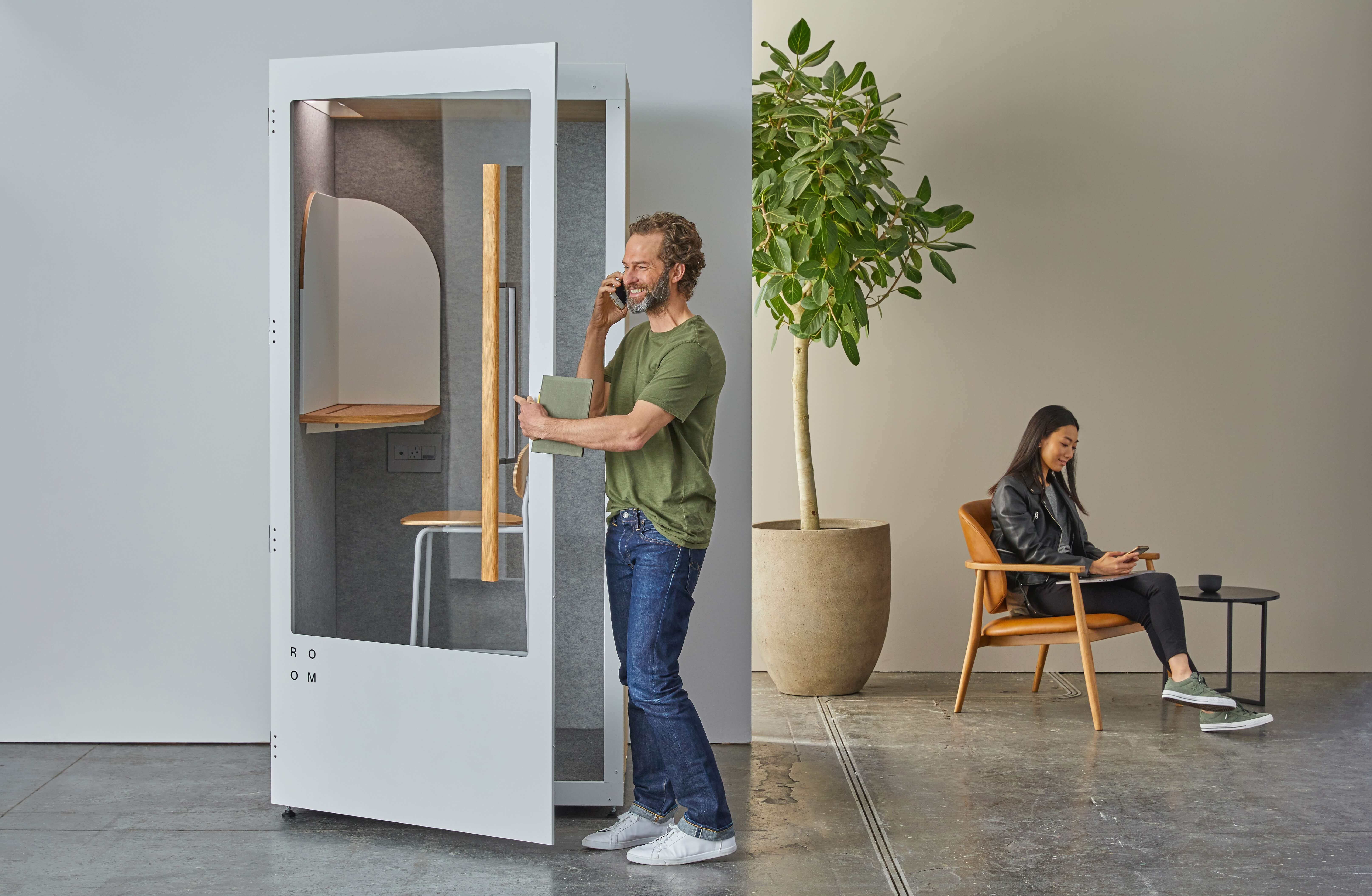 man on phone in acoustic office soundproof pod